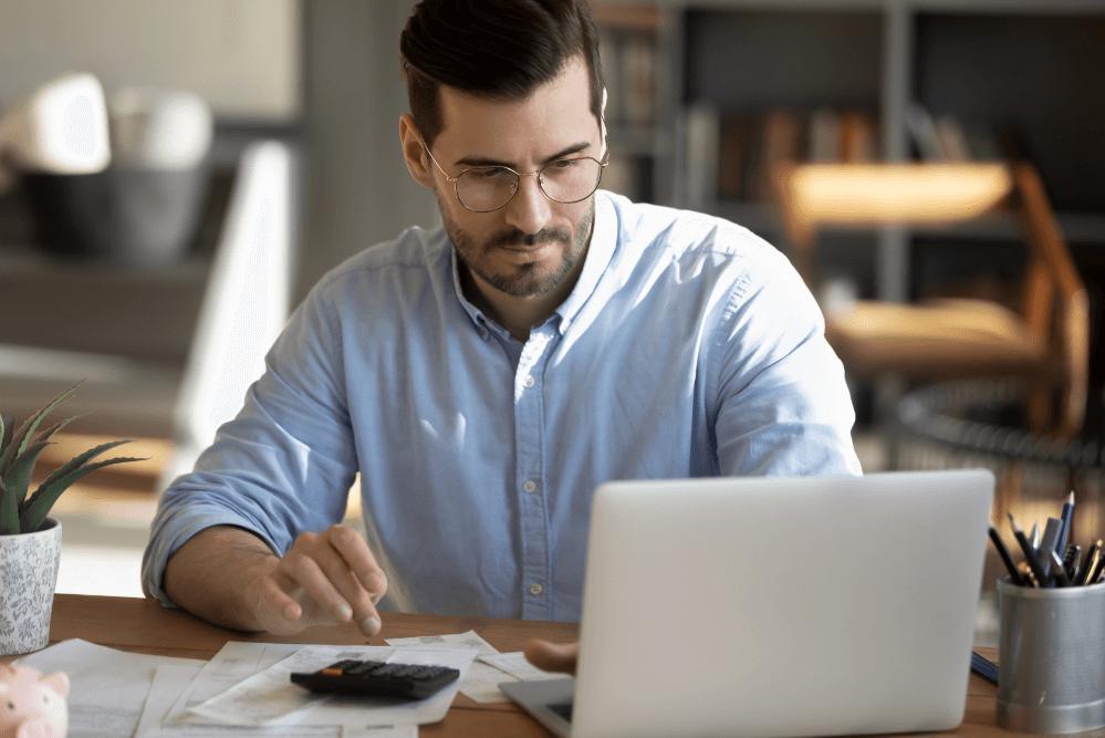 Mann am Laptop berechnet Wirtschaftlichkeit